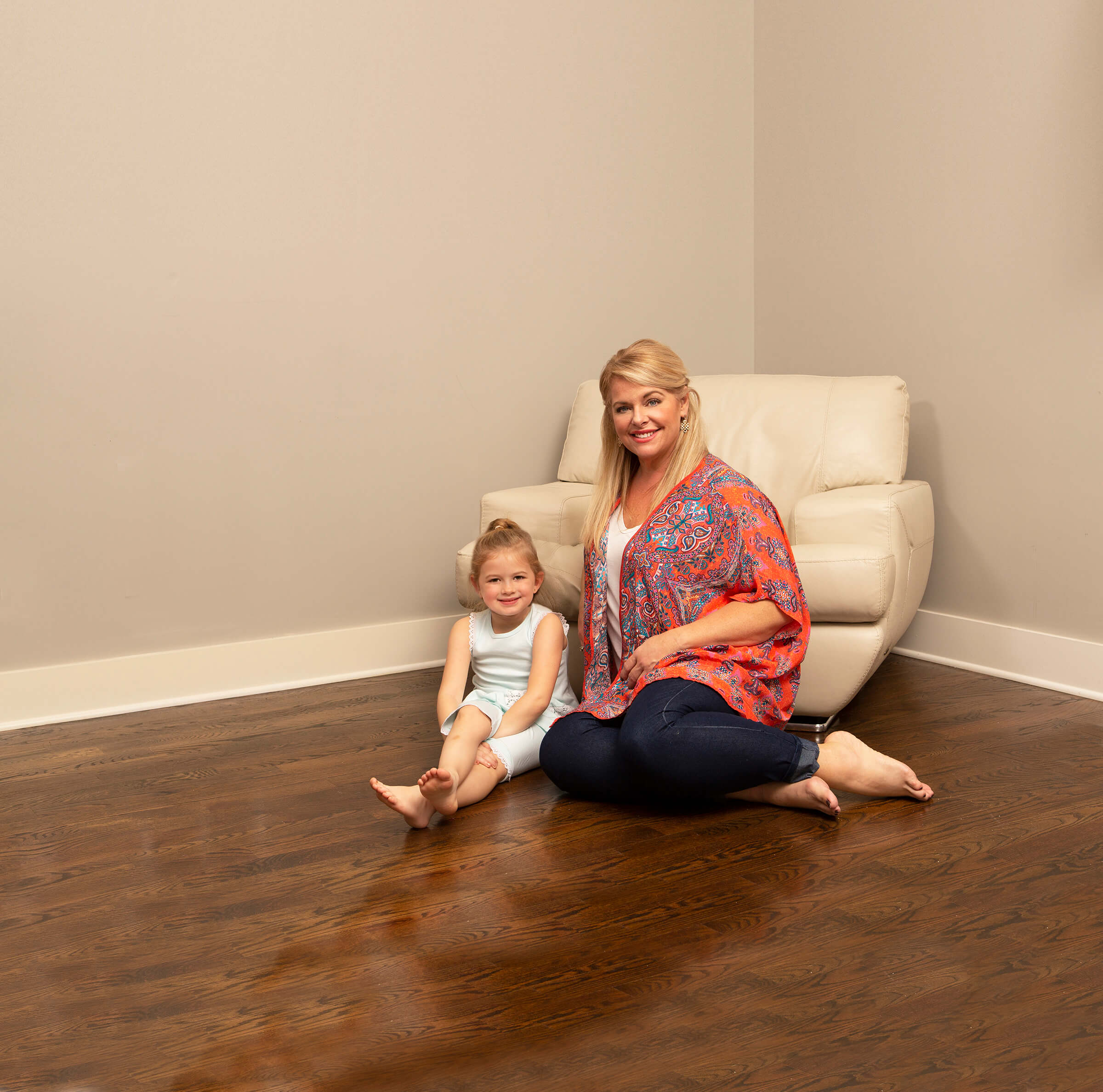 mother and daughter sitting on wood floor in gastonia home